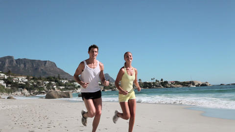 Young couple jogging on beach Stock Video Footage
