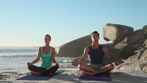 Young couple doing yoga on beach Stock Video Footage