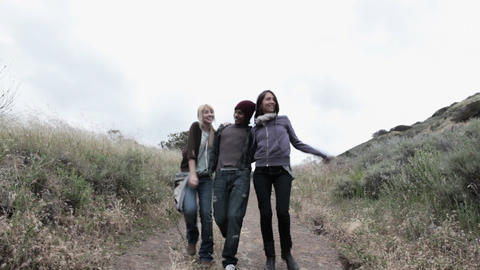 Three young friends walking down path, front view Stock Video Footage