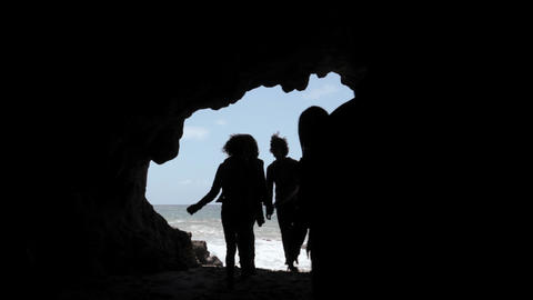 Group of young friends entering cave Stock Video Footage