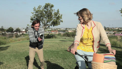 Man with video camera, following girlfriend as she cycles Stock Video Footage