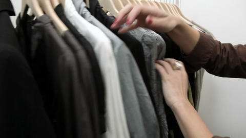 Woman looking through clothes on rail in boutique Stock Video Footage