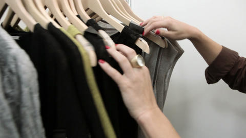 Woman looking through clothes on rail in boutique Footage