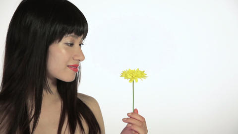Young woman smelling flower and putting it in her hair Stock Video Footage