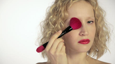 Young woman using make up brush on face Stock Video Footage