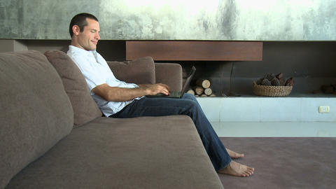 Man on sofa using laptop computer and smiling at camera Stock Video Footage