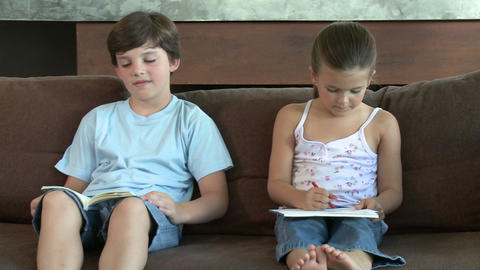 Brother and sister on sofa, reading and drawing Stock Video Footage