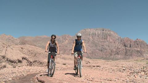 Couple mountain biking in rocky landscape Stock Video Footage