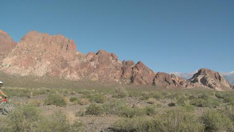 Couple mountain biking through rocky landscape Stock Video Footage