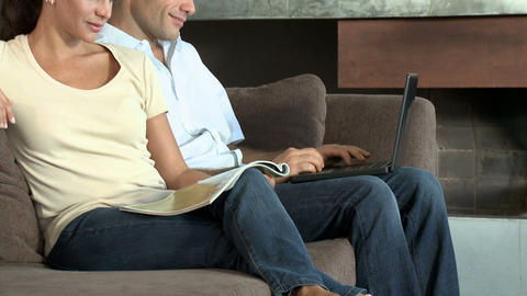 Couple on sofa, man using laptop and woman reading magazine Stock Video Footage