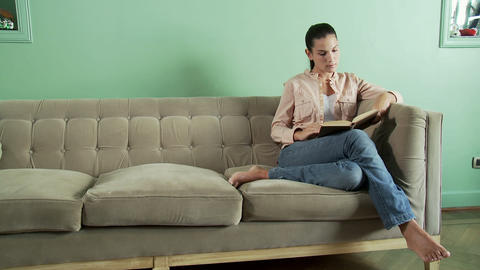 Young woman reading book on sofa Stock Video Footage