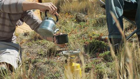 Zoom out from mann pouring drink from kettle to people... Stock Video Footage