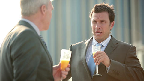 Businessmen talking and toasting with bucks fizz Stock Video Footage