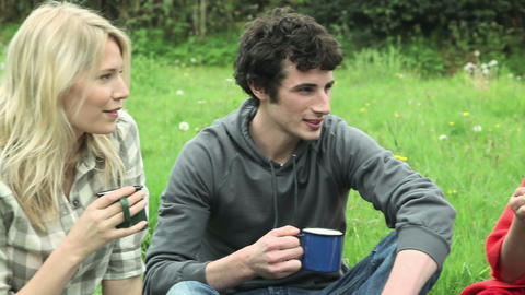 Friends in a field talking and holding cups Stock Video Footage
