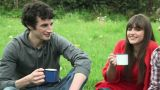 Friends in a field talking and holding cups Footage
