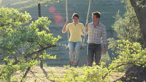 Couple on a swing on holiday Stock Video Footage