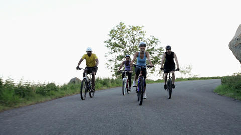 Four cyclists riding along road Stock Video Footage