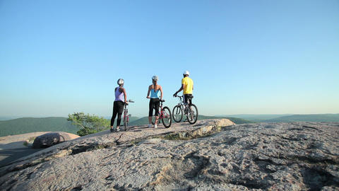 Three cyclists on rocks, scenic view Stock Video Footage