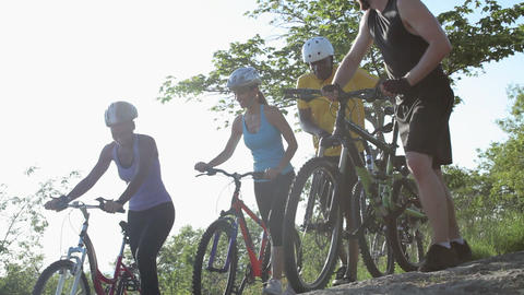 Four cyclists pushing bikes over rocks Stock Video Footage