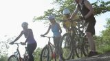 Four cyclists pushing bikes over rocks Footage