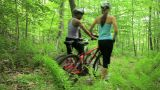 Female cyclists pushing bikes through forest Footage