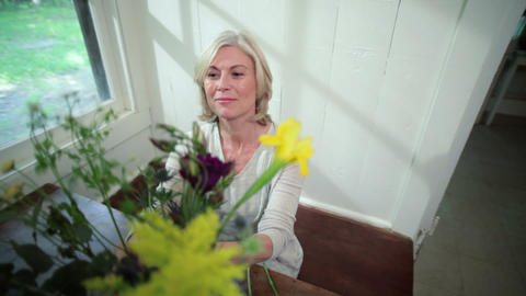 Mature woman arranging flowers Stock Video Footage