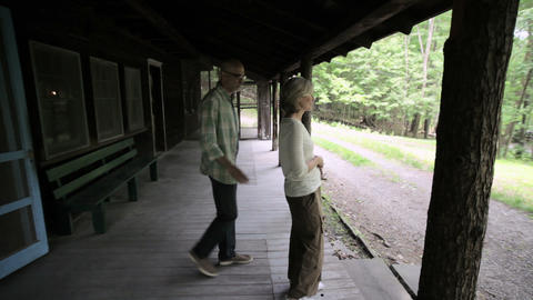 Mature couple on porch in rural retreat Stock Video Footage