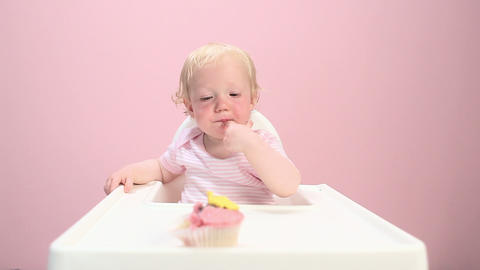Baby girl sitting in highchair eating cupcake Stock Video Footage