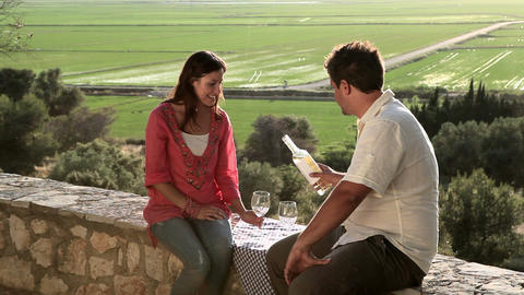 Young couple sitting on wall with wine Stock Video Footage