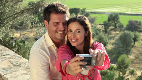 Young couple sitting on wall with camera Stock Video Footage