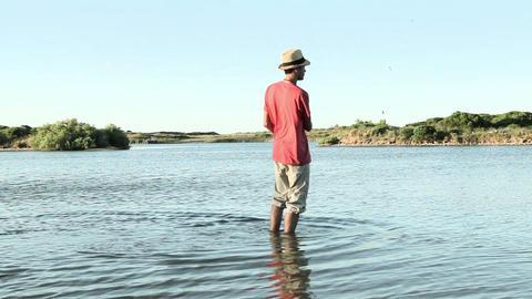 Teenage boy skimming stones in lake Stock Video Footage