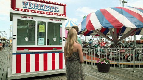 Teenage girl taking boyfriend to ticket booth in fun fair Stock Video Footage