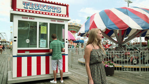 Teenage girl taking boyfriend to ticket booth in fun fair Footage