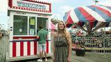 Teenage girl taking boyfriend to ticket booth in fun fair Footage