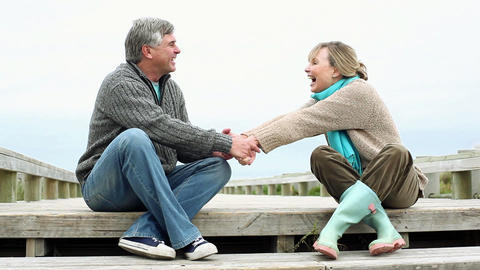 Couple sitting on coastal walkway, talking and holding hands Stock Video Footage