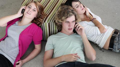 Three teenagers lying on floor using smartphones Stock Video Footage