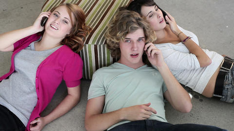 Three teenagers lying on floor using smartphones Stock Video Footage