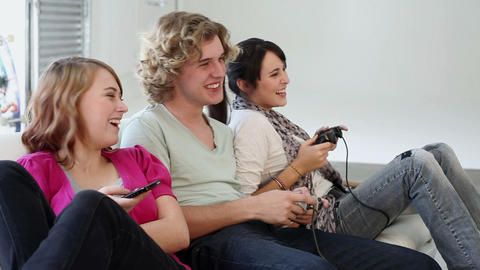 Three teenagers playing video game Stock Video Footage