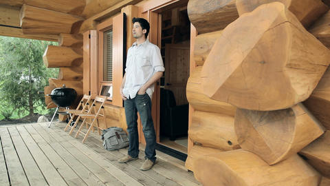 Young man coming out of log cabin Stock Video Footage