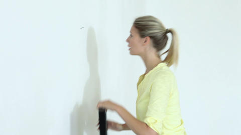 Young woman hammering nail into wall and hanging picture Stock Video Footage