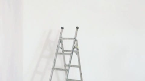 Young man using spirit level on wall Stock Video Footage
