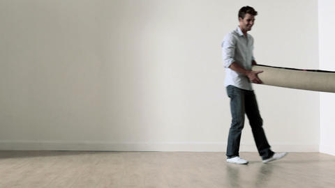 Couple unrolling rug on floor, man lies on it Stock Video Footage
