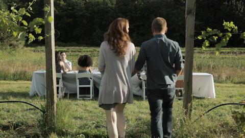 Young couple joining friends at farm dinner party Stock Video Footage