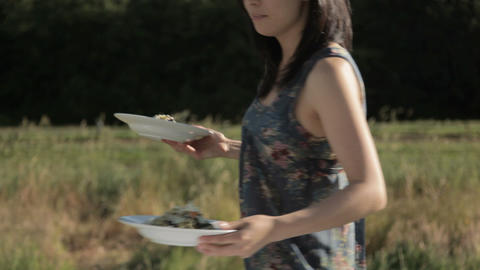 Young woman handing food to friends at outdoor dinner party Stock Video Footage