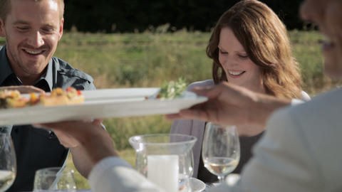 Friends sharing food at outdoor dinner party Stock Video Footage