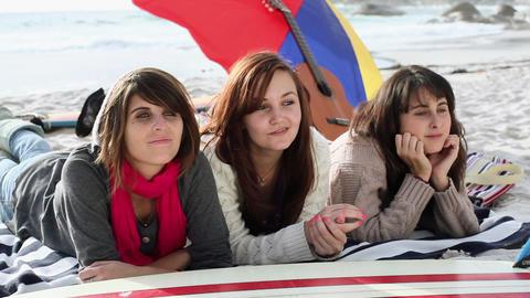 Three girls lying on the beach Stock Video Footage