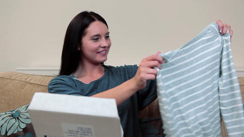 Young woman opening parcel containing clothing Stock Video Footage