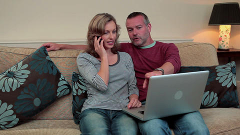 Mature couple using laptop, woman on mobile phone Stock Video Footage
