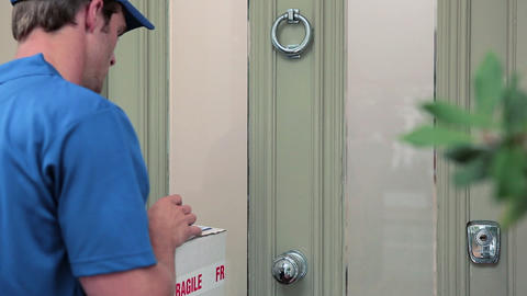 Delivery man knocking on front door, delivering parcel Stock Video Footage
