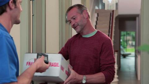 Delivery man knocking on front door, delivering parcel Stock Video Footage
